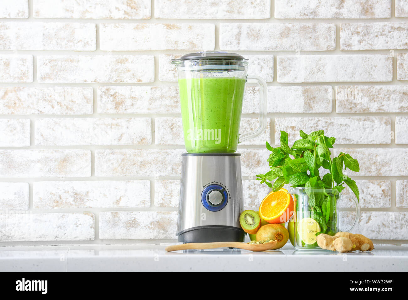 Blender with healthy smoothie and ingredients on table in kitchen Stock Photo