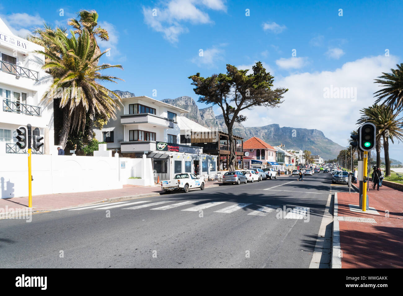 Camps Bay, upmarket suburb of Cape Town, South Africa, looking down the main road at shops, restaurants and apartments on a Spring day Stock Photo