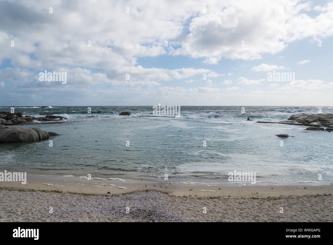 coastal tidal or tide pool at a white sandy beach on a cloudy Spring day in Camps Bay, Cape Town, South Africa with no people Stock Photo