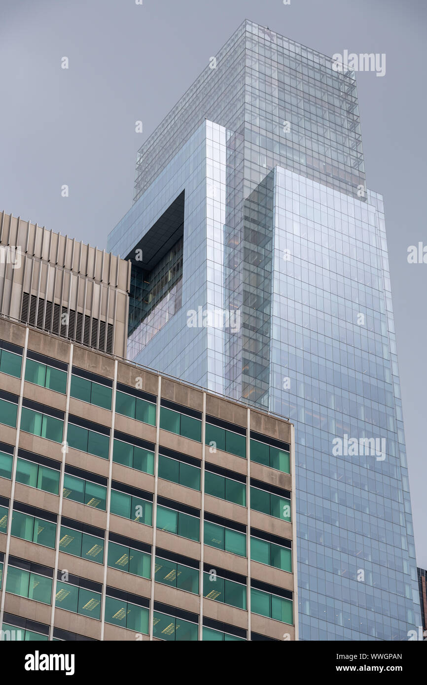 The sleek glass curtain wall of Philadelphia's tallest building, the Comcast Center, contrasts with the 1965 built 4 Penn Center office tower. Stock Photo