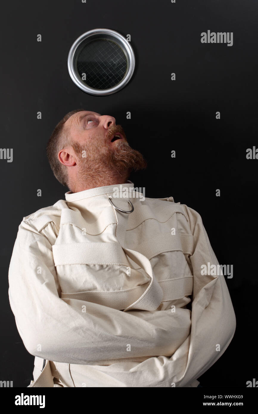 Photo of an insane man in his forties wearing a straitjacket crouched below the window of his cell. Stock Photo