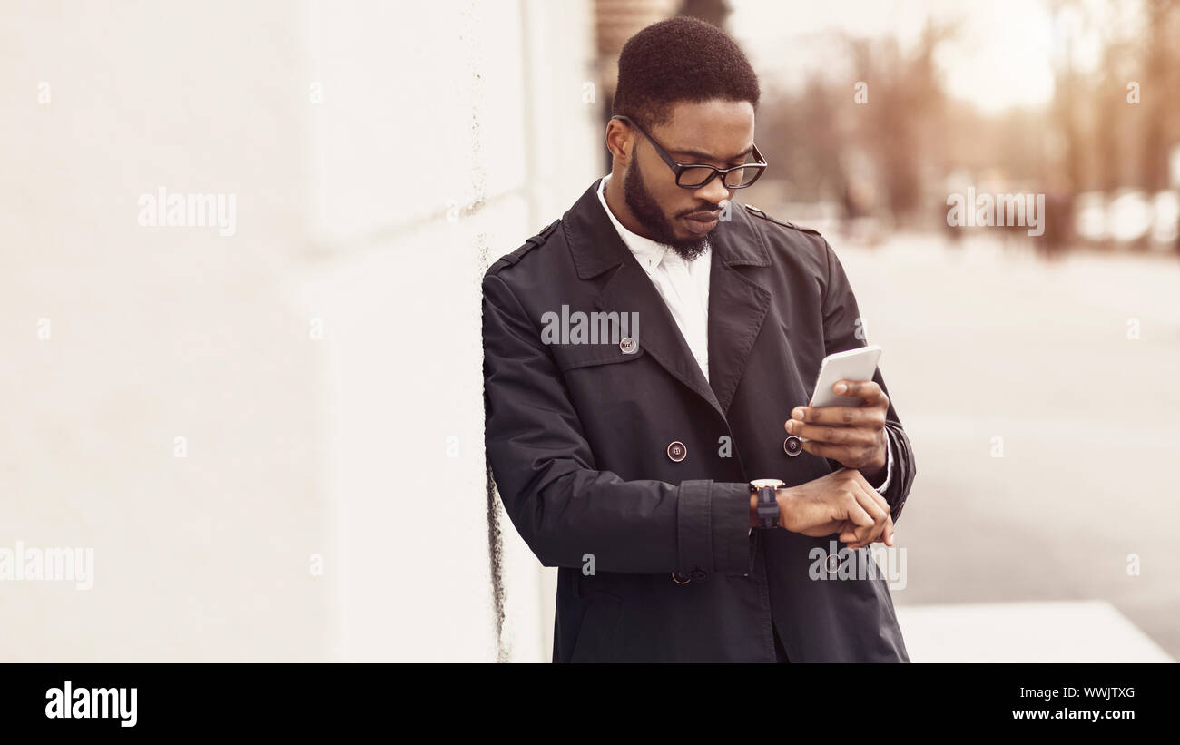 Millennial businessman looking at watches, waiting for colleague Stock Photo