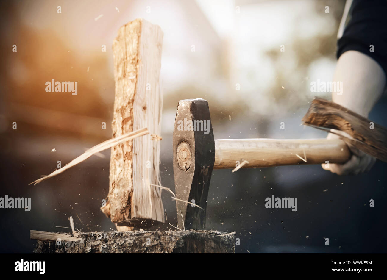 A powerful sharp axe cuts a log into pieces, from which small and large splinters fly in all directions. Stock Photo