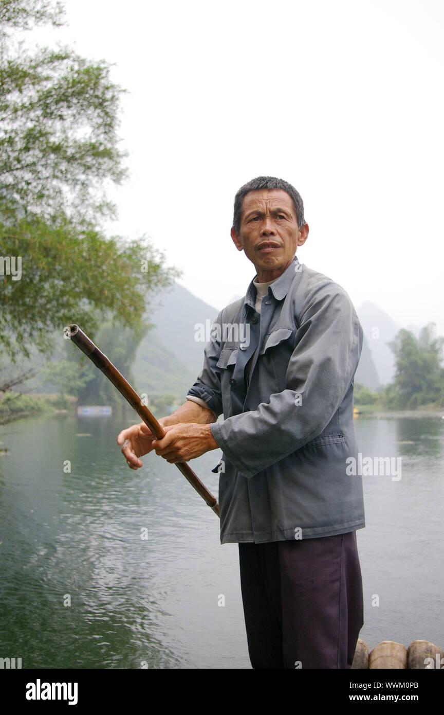 CHINA - MAY 16, A fisherman is paddling the bamboo boat along the Yulong River in Guilin, China on 15 May, 2010. Stock Photo