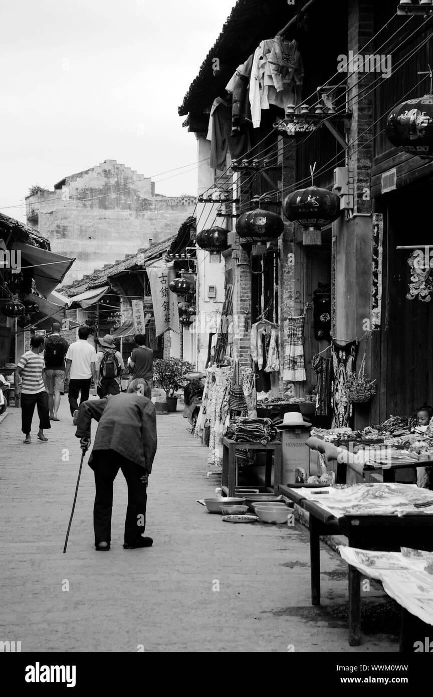 CHINA - MAY 17, An old woman is walking along the traditional street in Xingping, Yangshuo, China on 17 May, 2010. Stock Photo