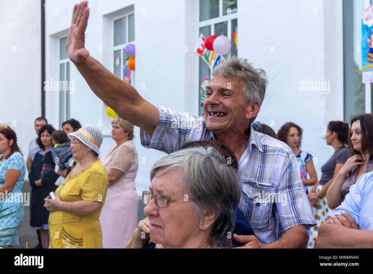 Adygea, Russia - September 2, 2019: Cheerful toothless man happily waving in the crowd Stock Photo