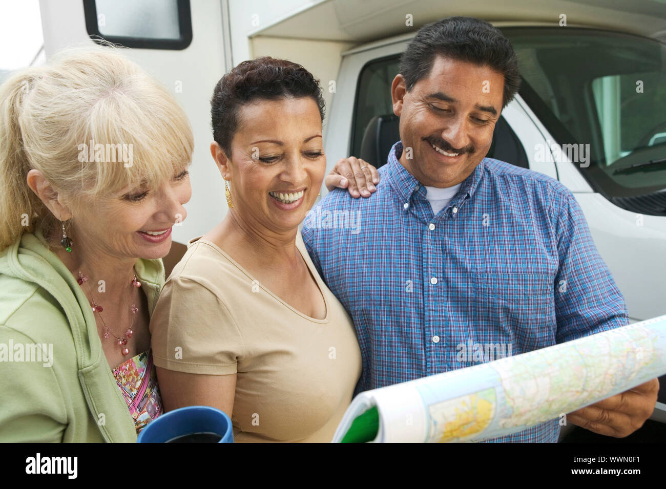 Friends Consulting Road Map During RV Trip Stock Photo