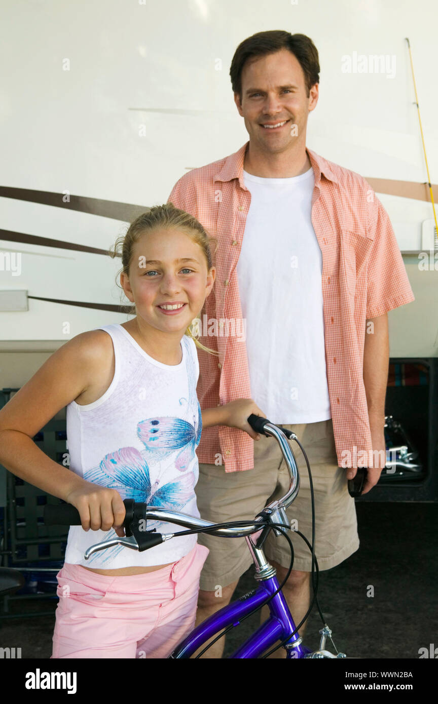 Father with Daughter on Bike Next to RV Stock Photo