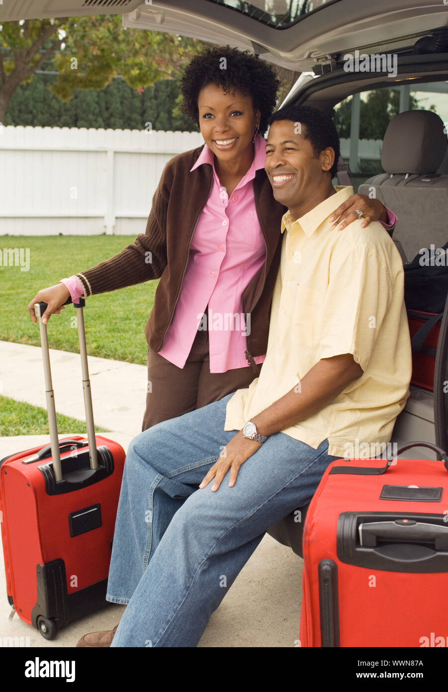 Couple and Luggage Standing by Minivan Stock Photo