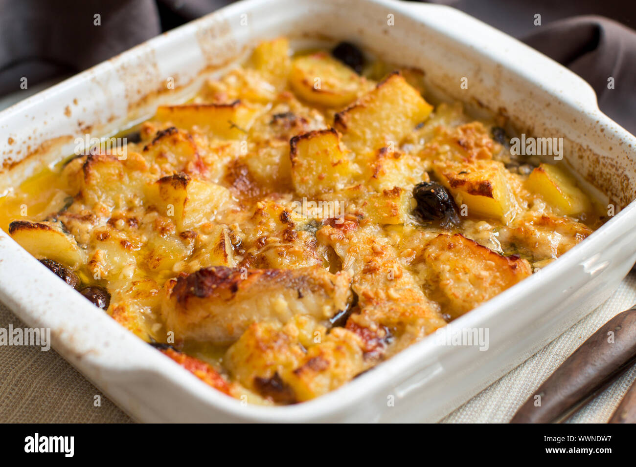 Fish with potatoes  and olives cooked in oven in small casserole Stock Photo