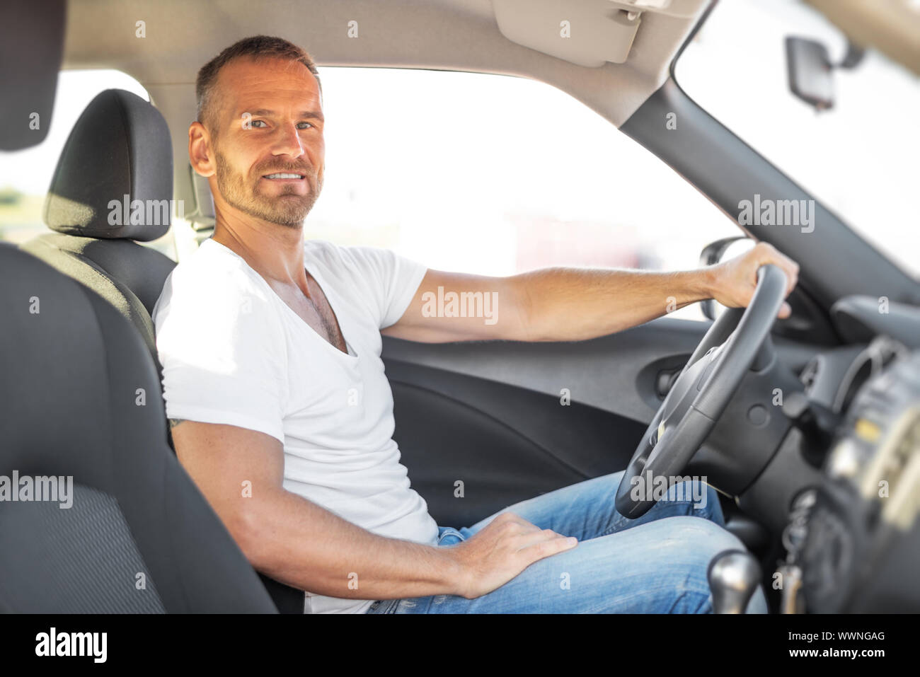 A man driving a white car. Stock Photo
