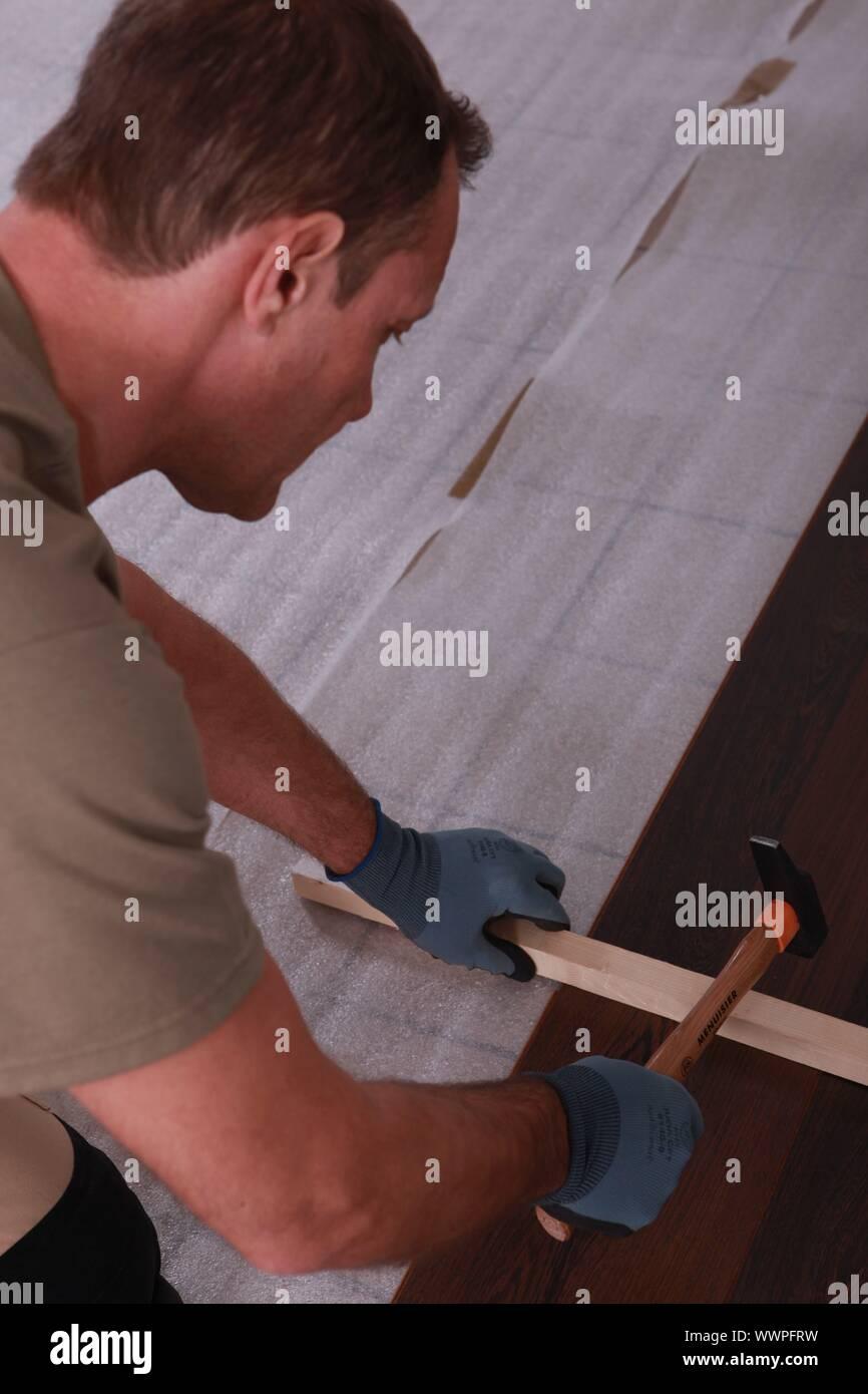 a handyman putting floorboards Stock Photo