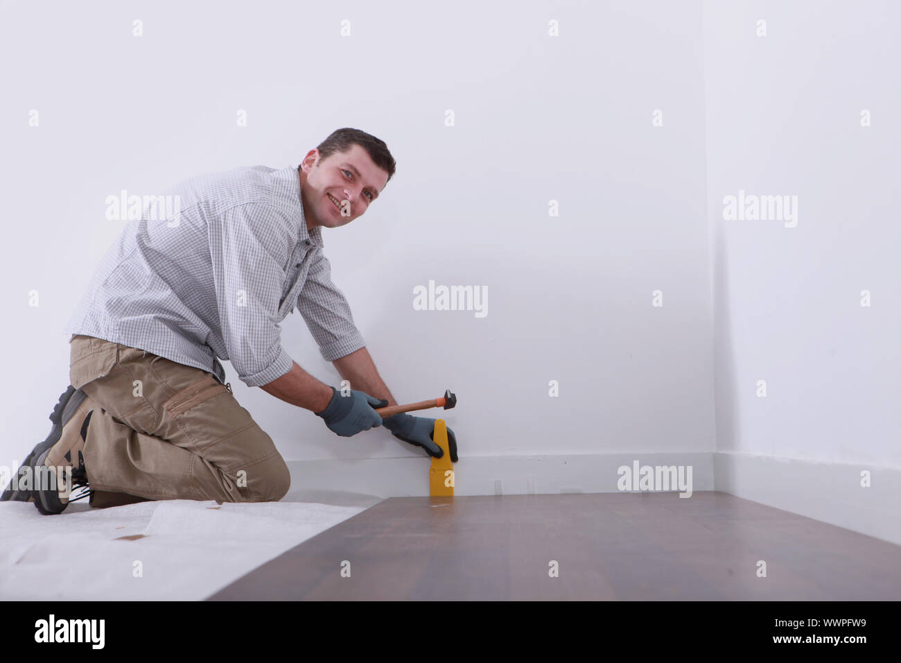 a man laying floorboards Stock Photo