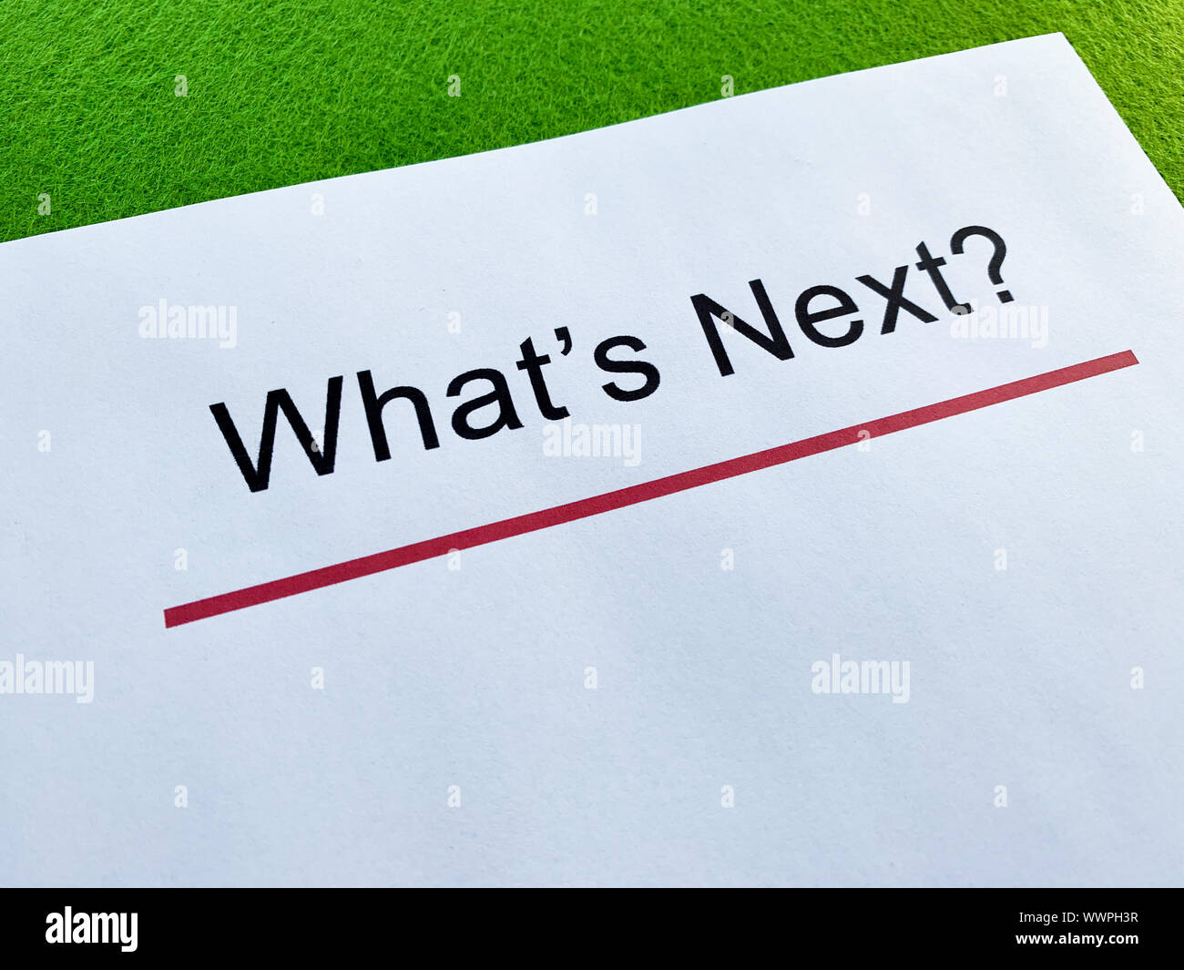 Clipboard with text what's next on green desk. Stock Photo