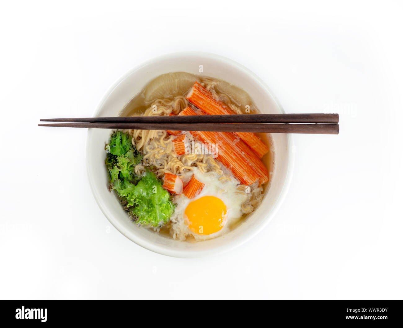 Bowl of instant noodles with crab sticks and eggs isolated on a white background Stock Photo