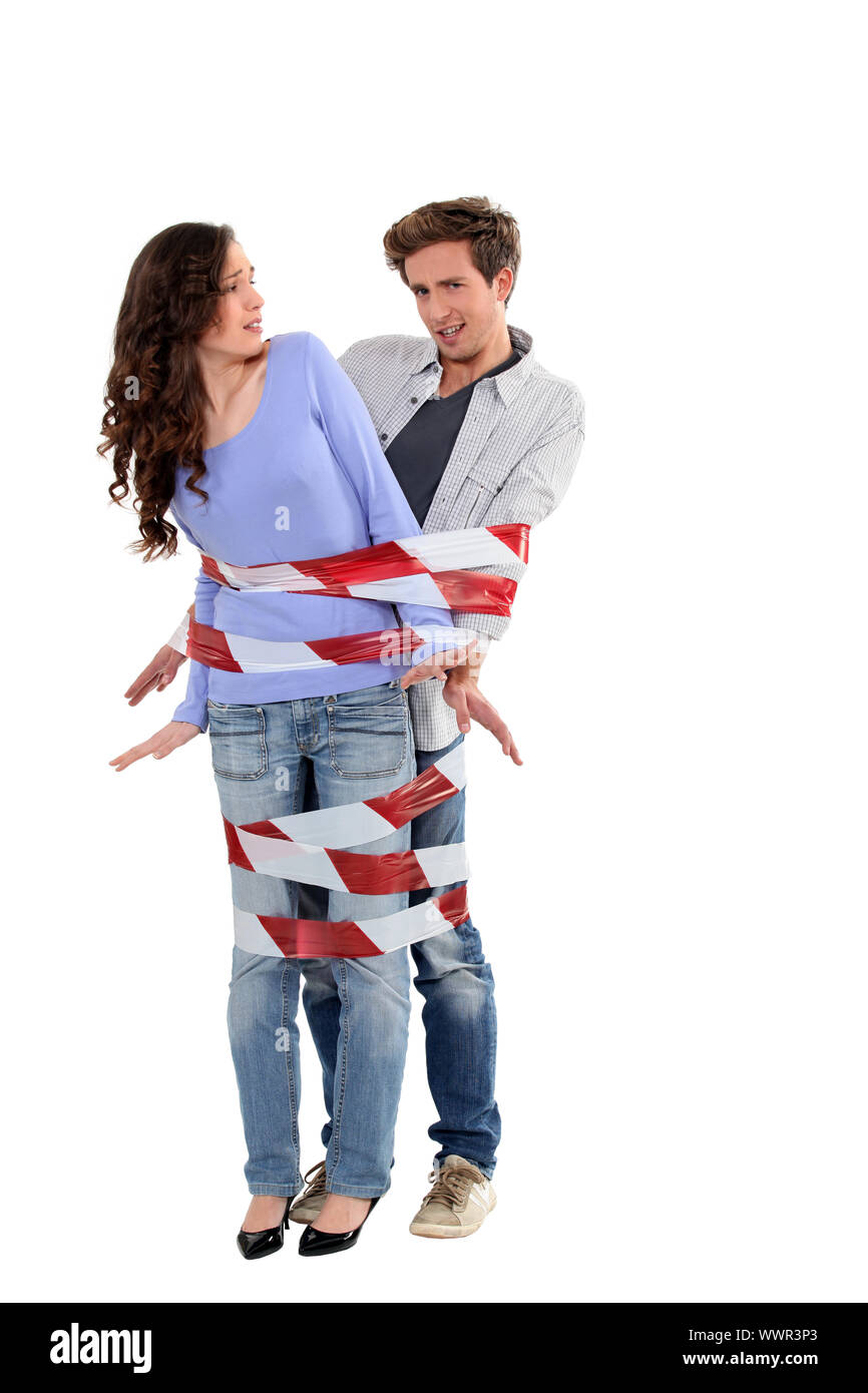 Couple being forcibly held together by caution tape Stock Photo