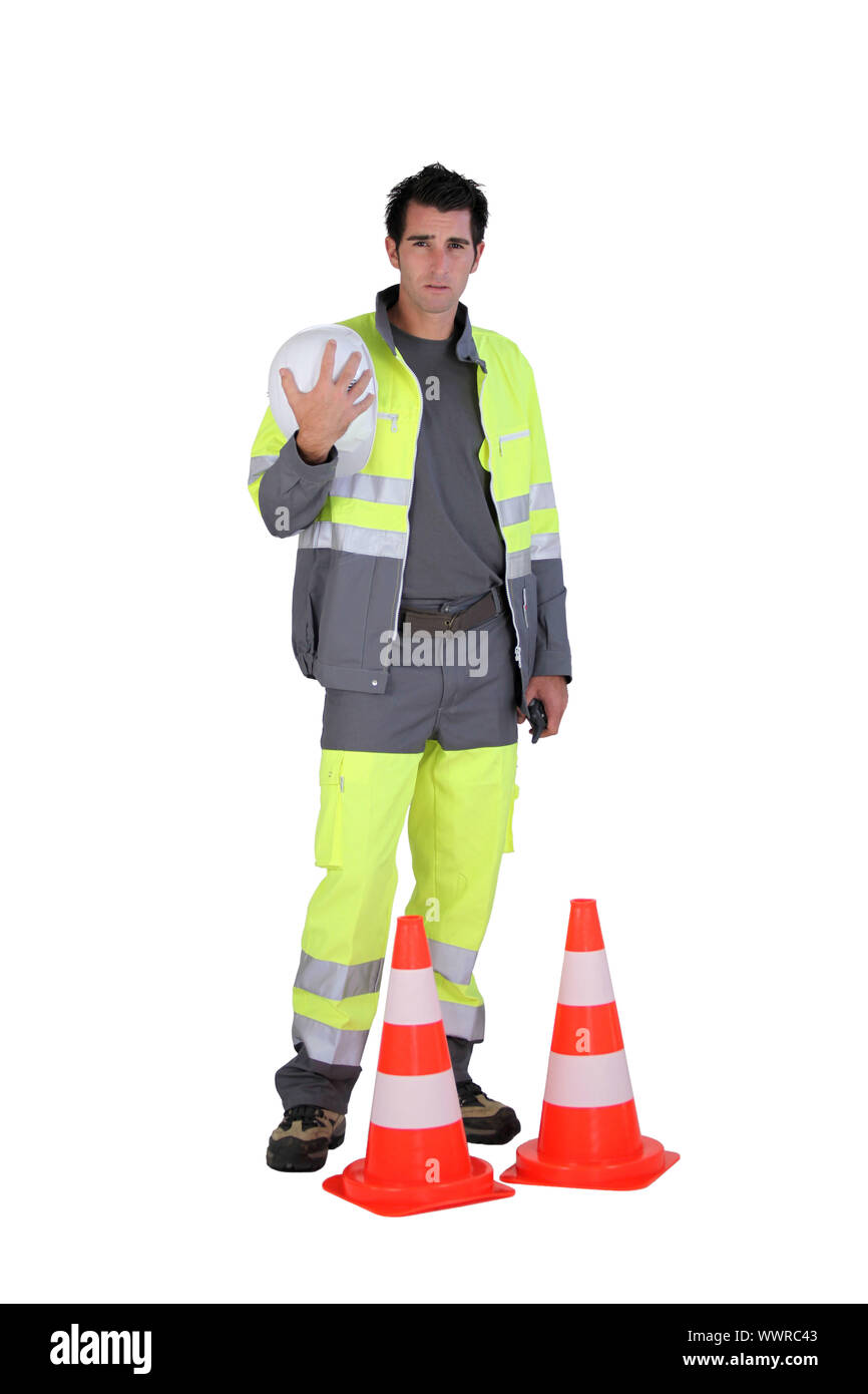Traffic worker stood by cone Stock Photo