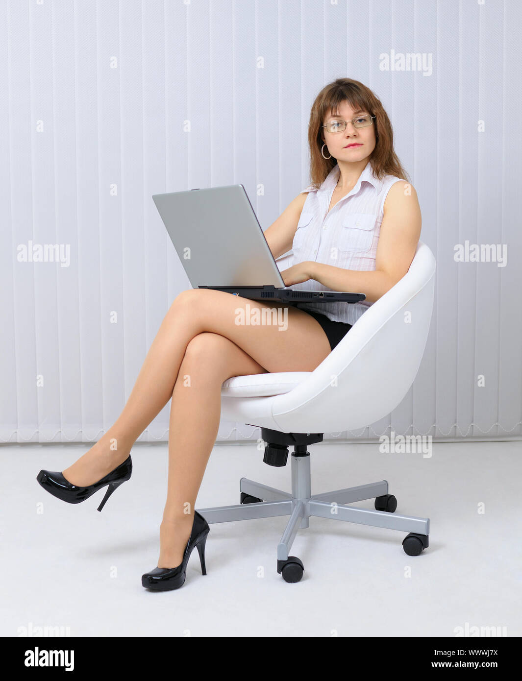 Very serious, beautiful young woman sitting in a white chair with laptop Stock Photo