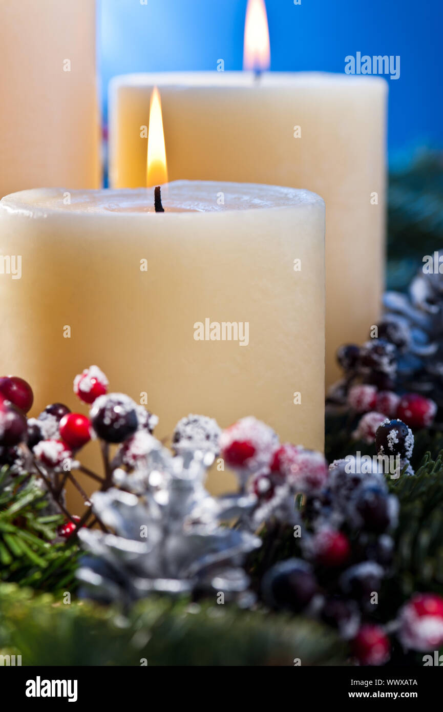 Three burning candles in an advent flower arrangement Stock Photo