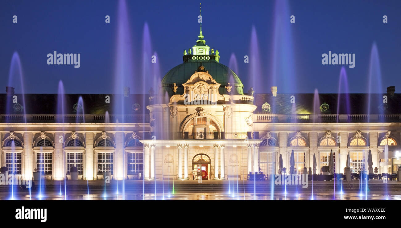 illuminated Kaiserpalais with water columns in the spa park at blue hour, Bad Oeynhausen, Germany Stock Photo