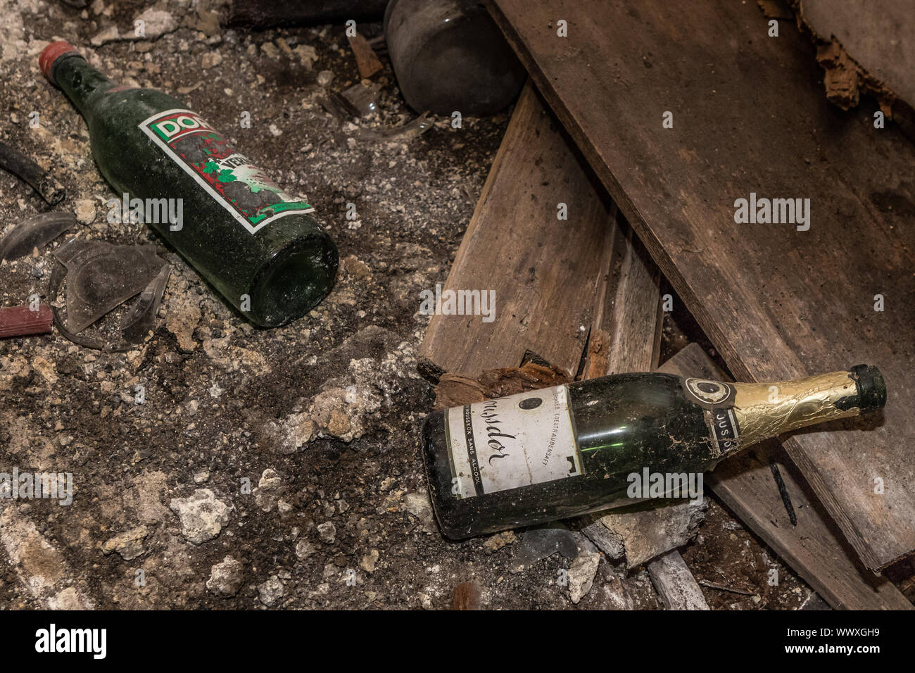 Two champagne and wine bottles are on the floor - Lost Place Stock Photo