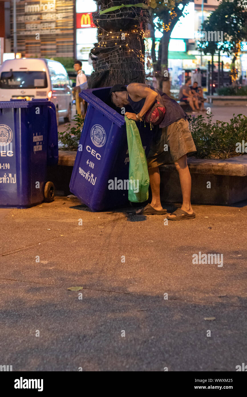 Homeless man looking for plastic waste for recycling  in Chiangmai Thailand. Stock Photo