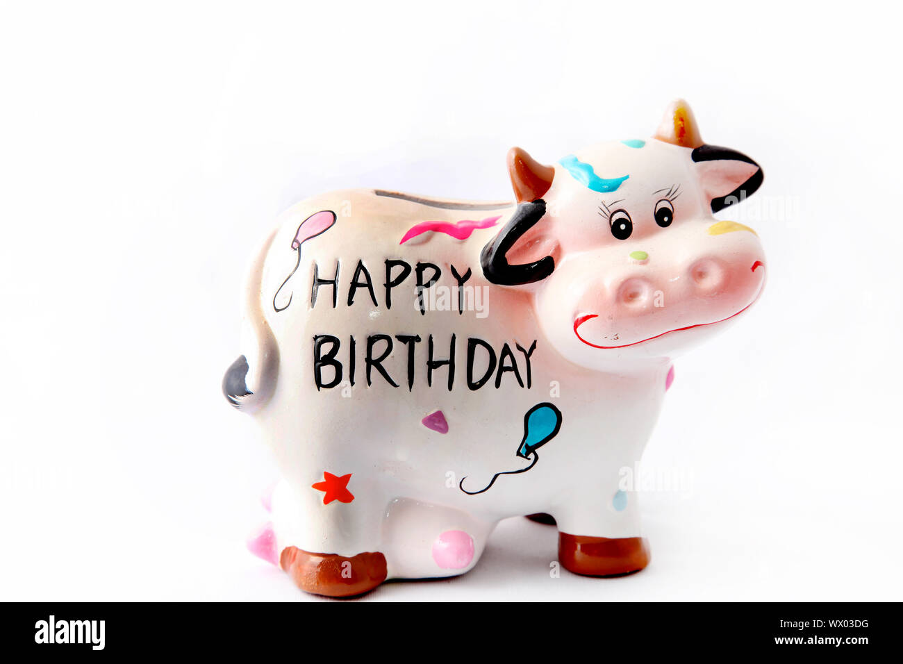 "a cheerful brindled cow with the slogan ""Happy Birthday"" on his stomach Stock Photo"