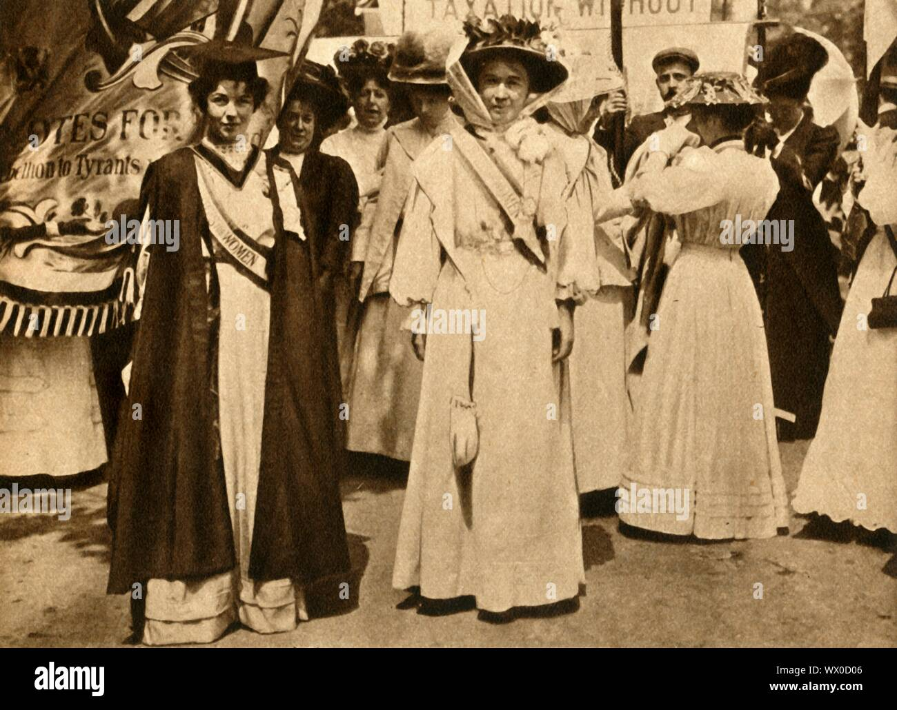 """Christabel Pankhurst and Emmeline Pethick-Lawrence, Hyde Park, London, 21 June 1908, (1933). British suffrage campaigners Christabel Pankhurst (1880-1958) and Emmeline Pethick-Lawrence (1867-1954) at a rally on 'Women's Sunday'. Suffragettes protested through direct action and civil disobedience, achieving partial suffrage in 1918. It was not until 1928 that all women finally gainied the right to vote. From """"The Pageant of the Century"""". [Odhams Press Ltd, 1933] Stock Photo"""