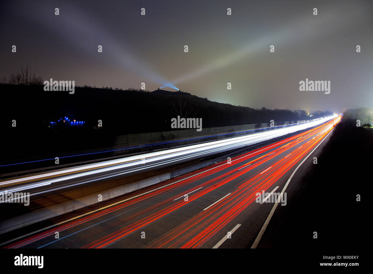 light streaks on highway A2 and the light beams on stockpile Rungenberg, Gelsenkirchen, Germany Stock Photo
