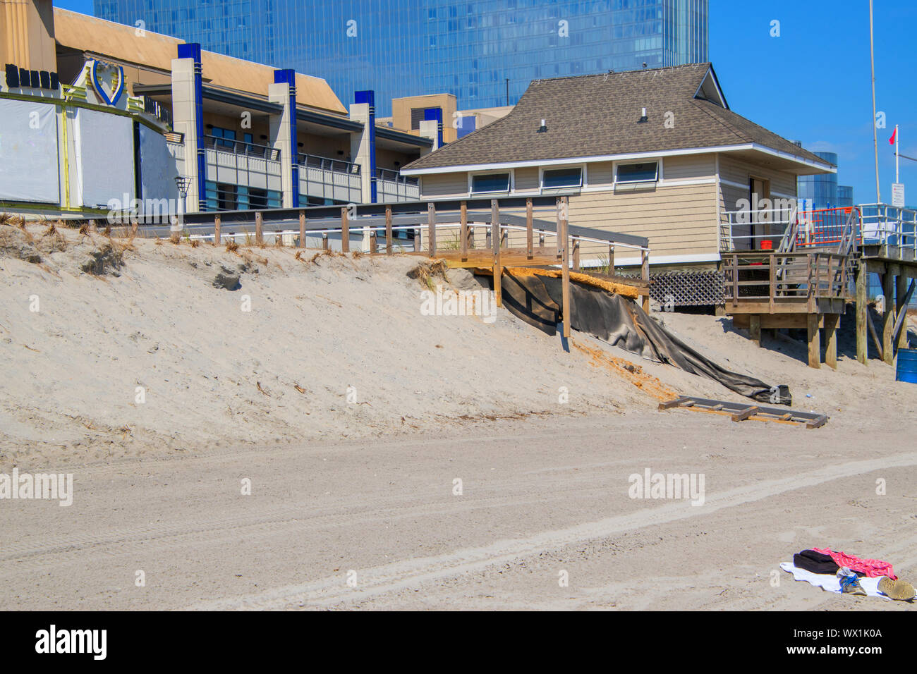 Erosion of the sand of the beach with destruction of a asphalt path near a raised lifeguard station after a hurricane and storm Stock Photo