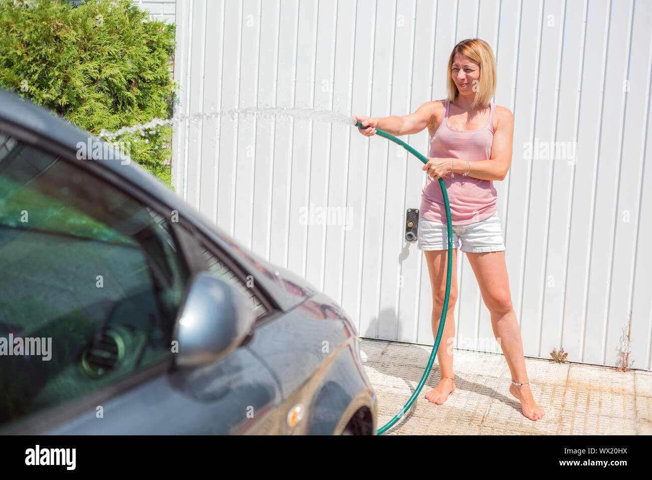 Young woman washing car with hose. Car detailing. Stock Photo