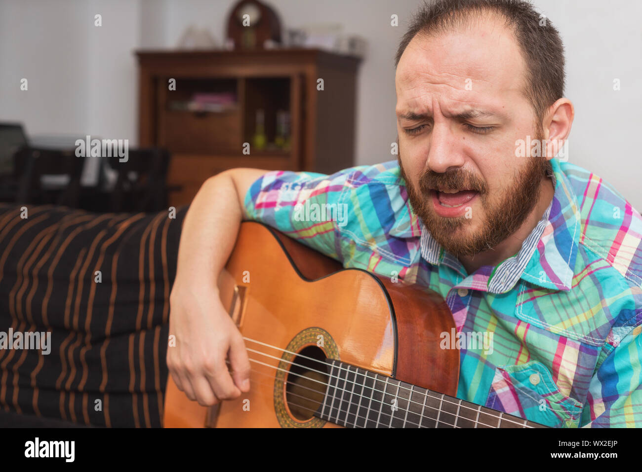Young man musician playing acoustic guitar - Stock Photo