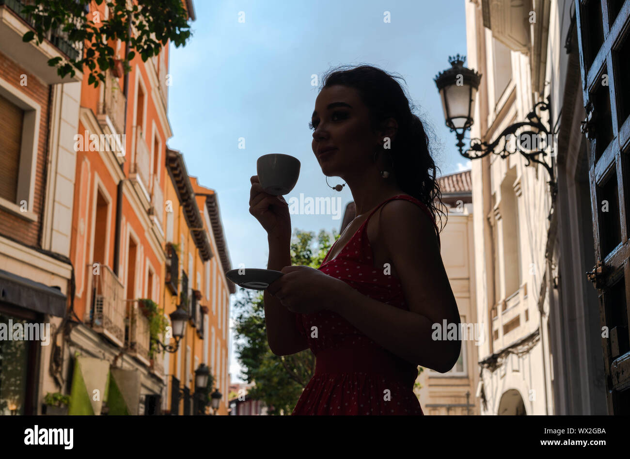 Beautiful young woman enjoying coffe cup and looking at street of European old town at morning time. Having break or breakfast. Stock Photo
