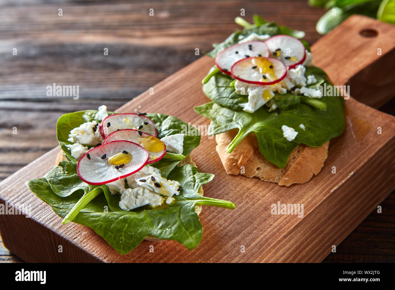 Ciabatta toasts with soft cottage cheese, slices of radish, fresh spinach, flax seeds on wooden background. Stock Photo