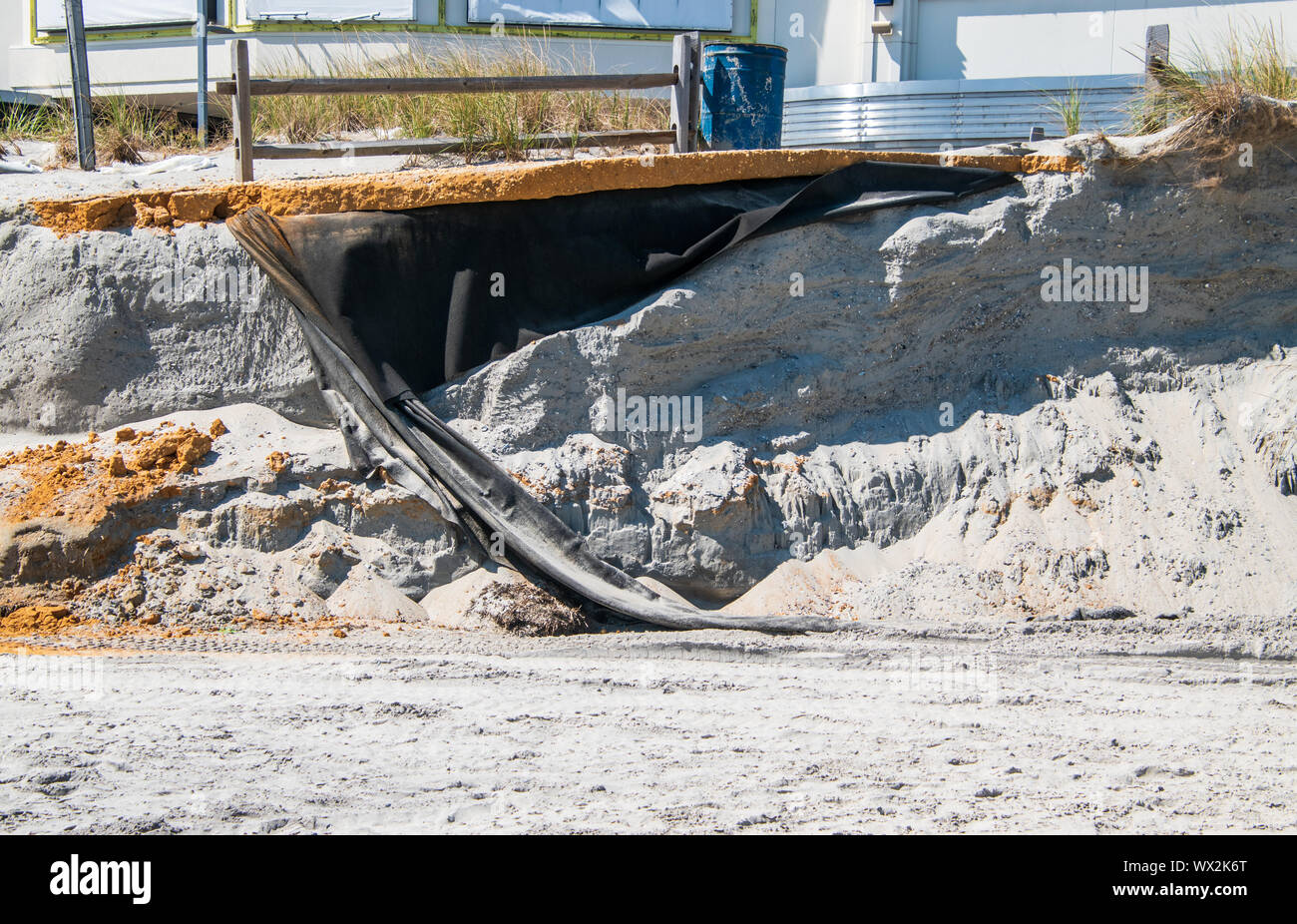 Erosion of the sand of the beach with destruction of a asphalt path after a hurricane and storm. Stock Photo