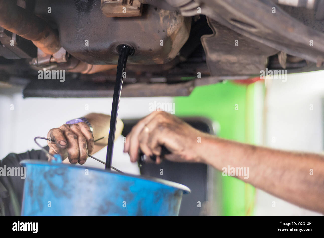 Mechanic emptying the oil in a bucket Stock Photo