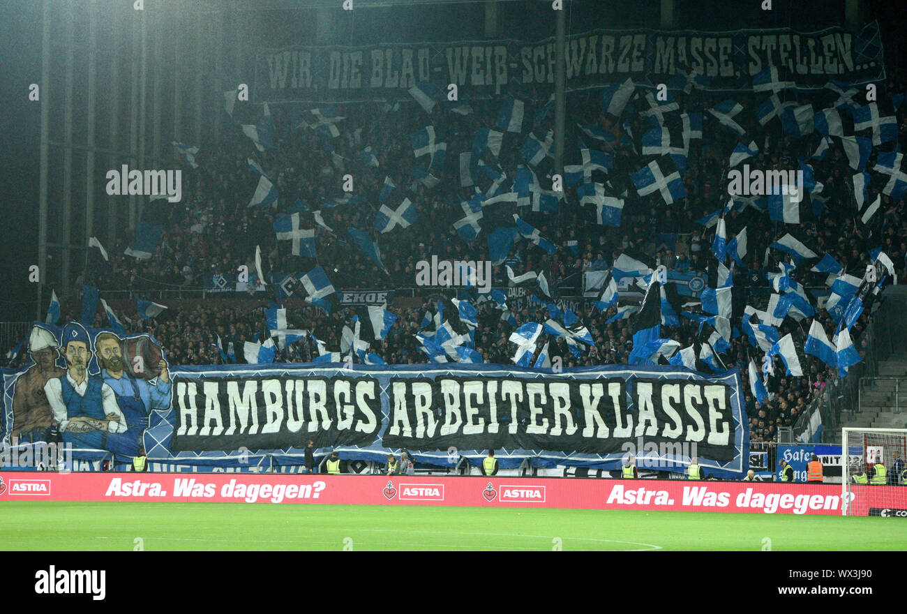 """Hamburg, Germany. 16th Sep, 2019. Soccer: 2nd Bundesliga, 6th matchday FC St. Pauli - Hamburger SV at Millerntor Stadium. Fans of HSV in the stands at a fan choreography with the lettering """" We, the blue-white-black mass, present . Hamburg's """"working class"""" on banners. IMPORTANT NOTE: In accordance with the requirements of the DFL Deutsche Fußball Liga or the DFB Deutscher Fußball-Bund, it is prohibited to use or have used photographs taken in the stadium and/or the match in the form of sequence images and/or video-like photo sequences. Credit: Daniel Bockwoldt/dpa/Alamy Live News Stock Photo"""