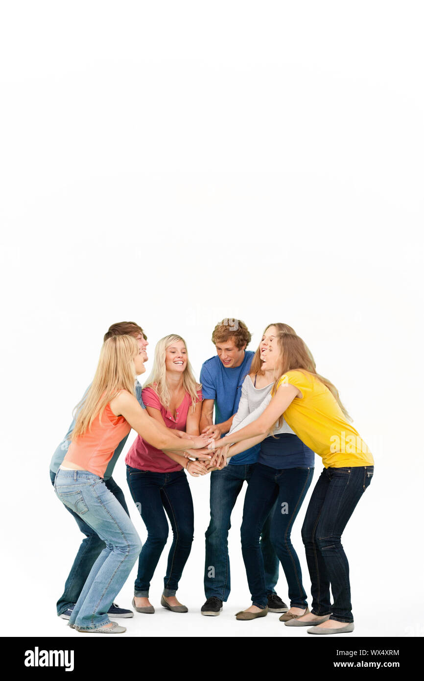 Group of friends about to cheer with their hands stacked smiling as they look at one another Stock Photo