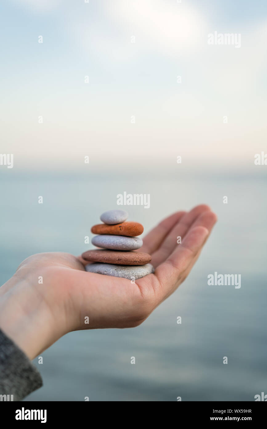 Pile of stacked stones in human hand Stock Photo
