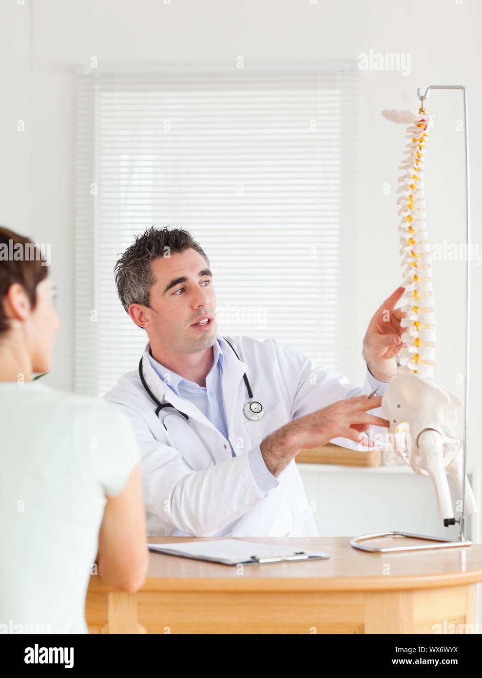 Doctor showing a female patient a part of a spine in a room Stock Photo