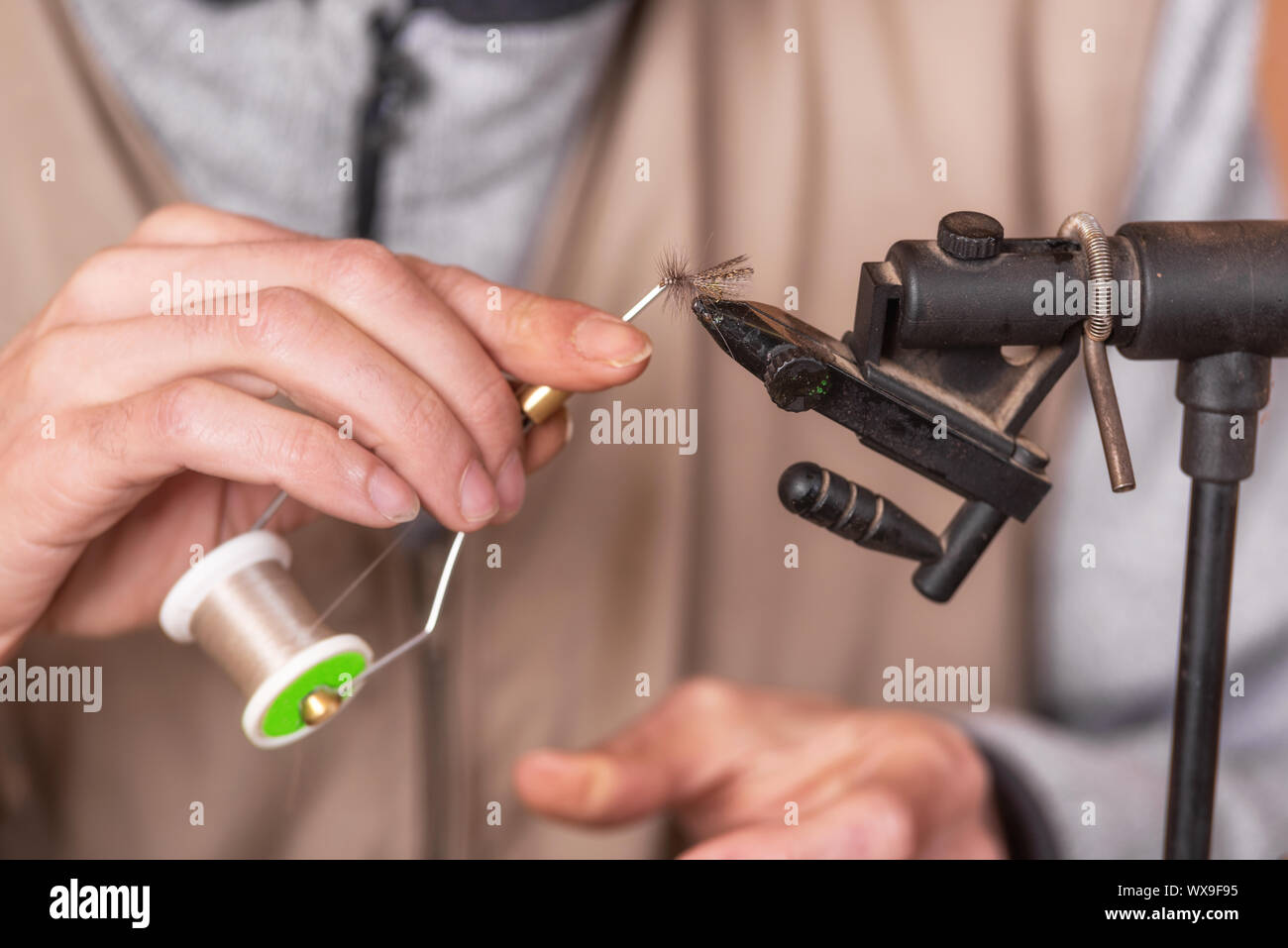 Close up of fisherman tying a fly for fishing. Stock Photo