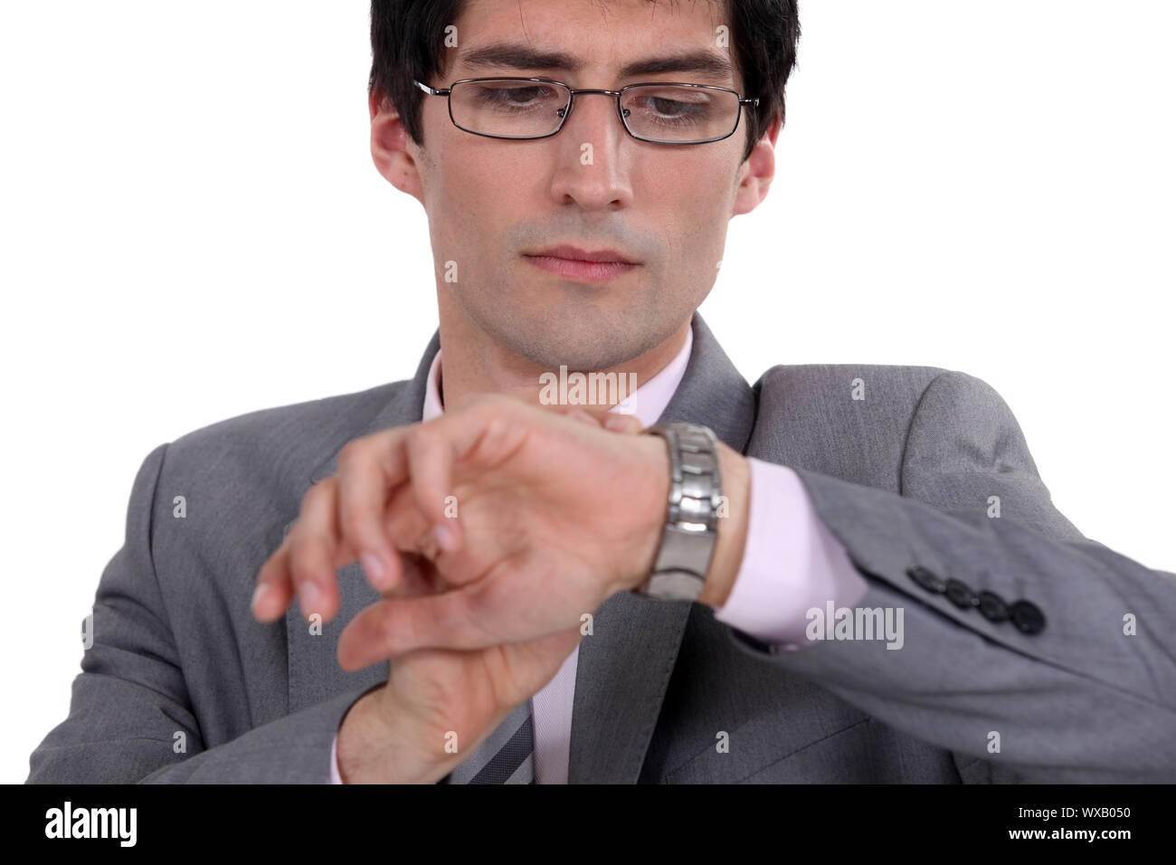 Businessman checking time on wrist watch Stock Photo