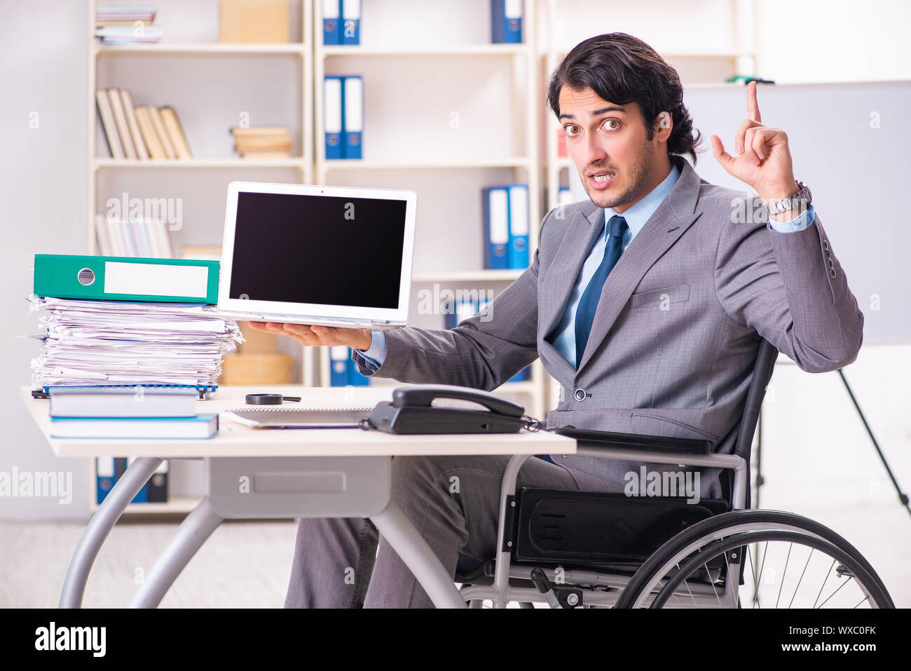 Young handsome employee in wheelchair at the office Stock Photo