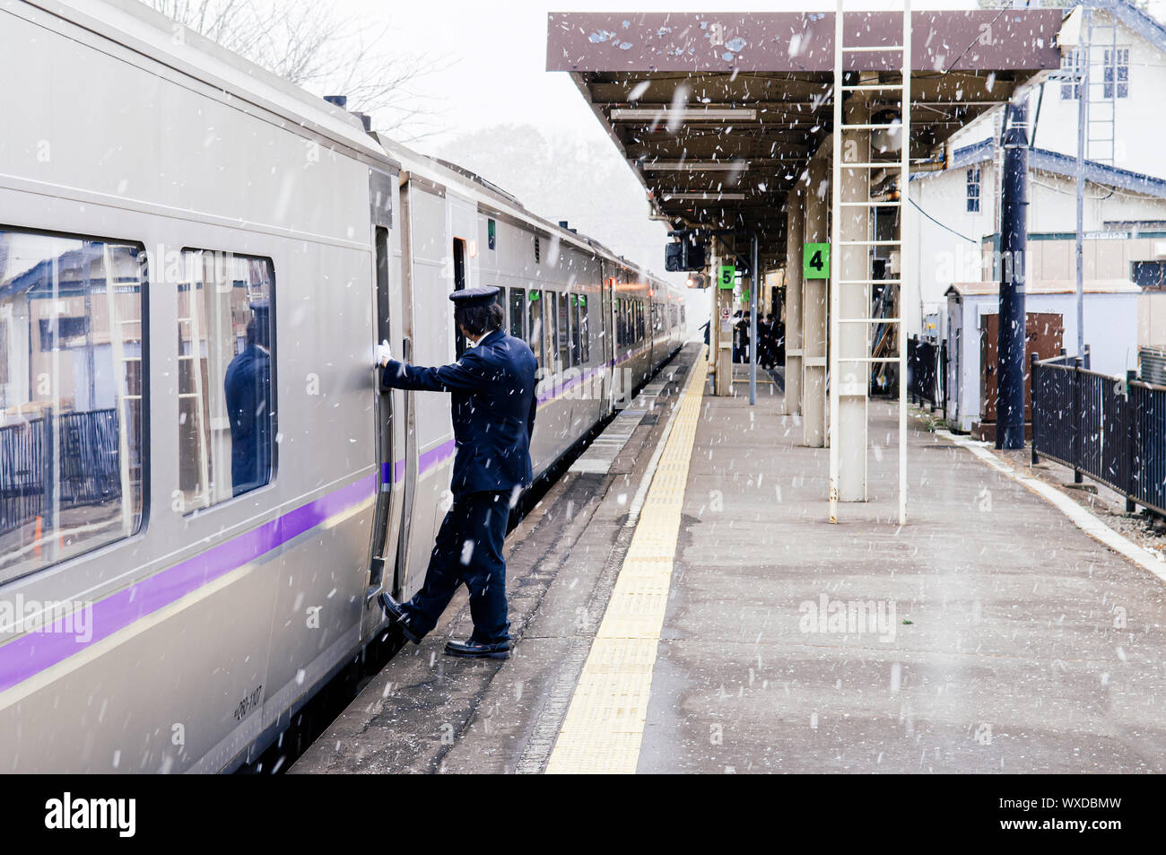 DEC 1, 2018 Hakodate, JAPAN - JR Suoer Hokuto train stop at Onuma Koen station  platform during snow fall in winter with train conductor staff stand a Stock Photo