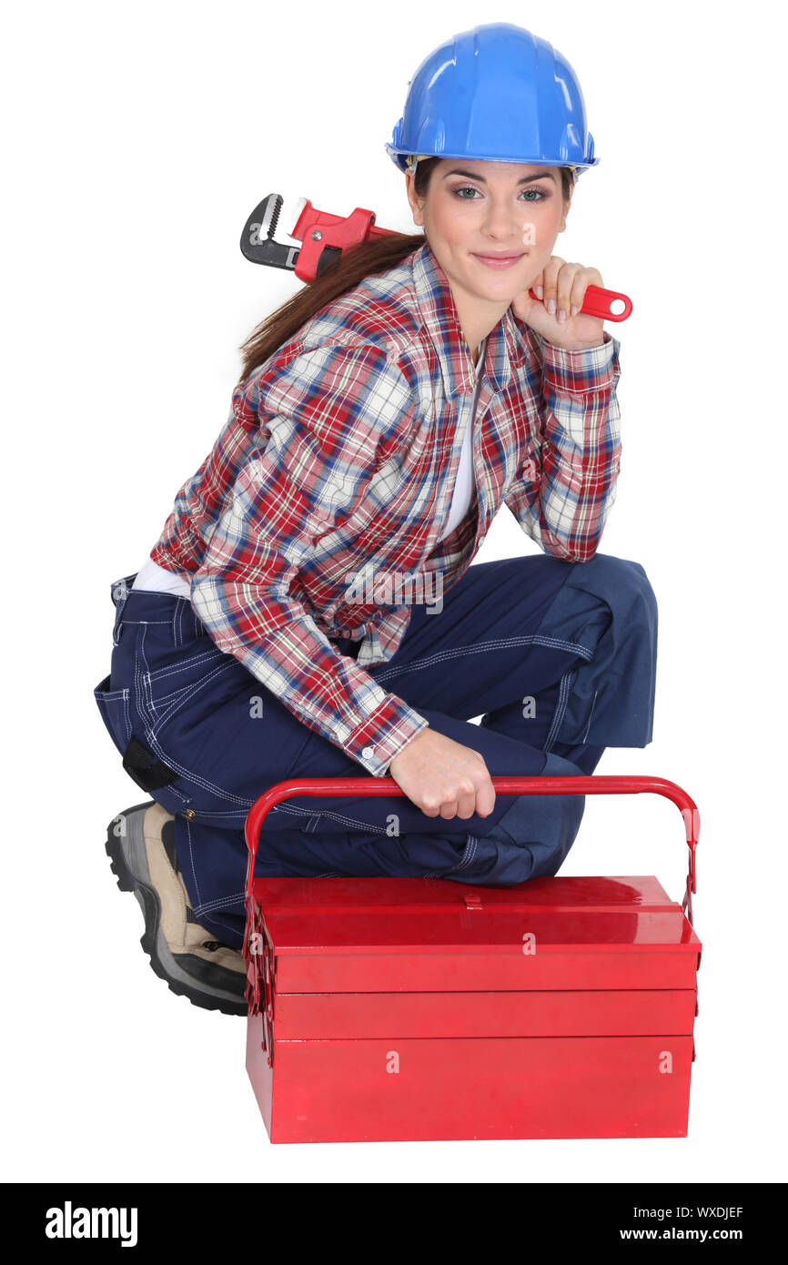 Portrait of a tradeswoman with a pipe wrench and a toolbox Stock Photo