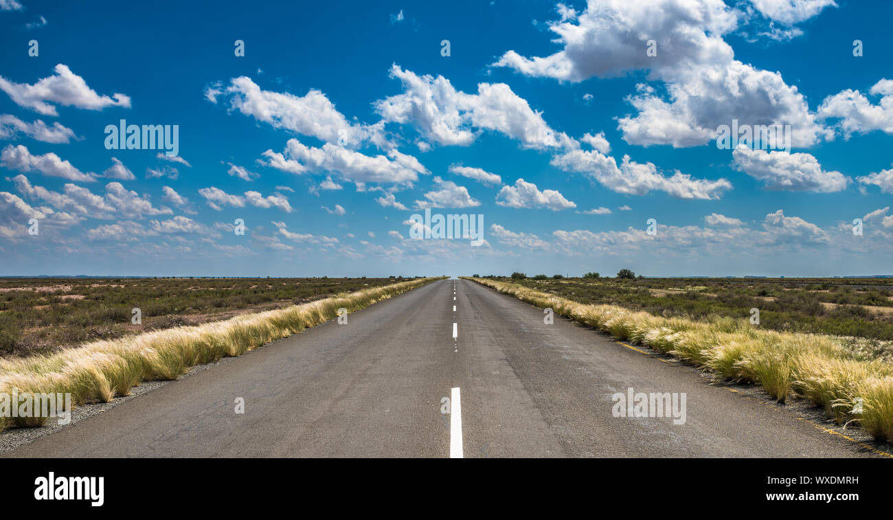 vibrant image of desert road and blue cloudy sky Stock Photo