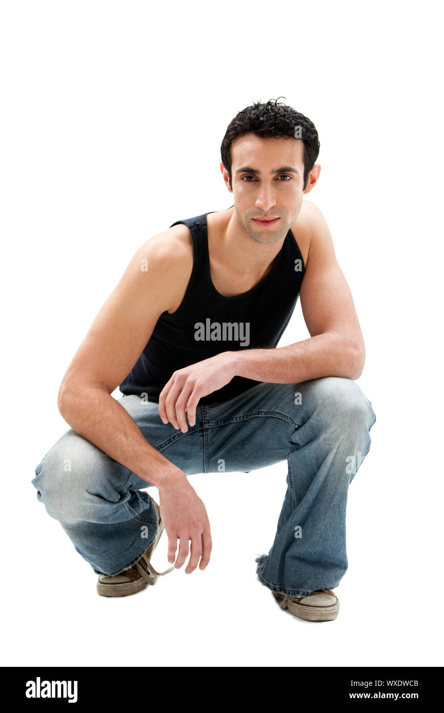 Handsome serious Caucasian guy wearing black tank top and jeans squatting, isolated Stock Photo