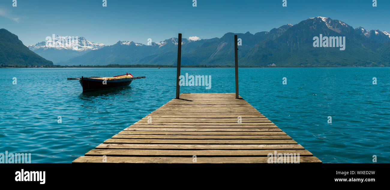 Montreux, VD / Switzerland - 31 May 2019: mountain and lake landscape with a vintage rescue rowboat Stock Photo