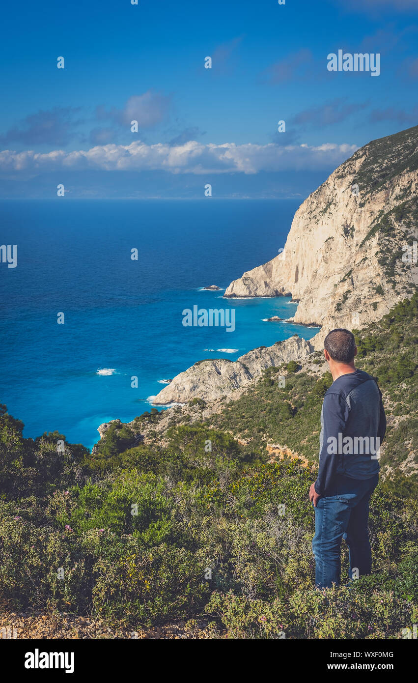 Tourist admiring view on the viewpoint above Navagio Beach Stock Photo