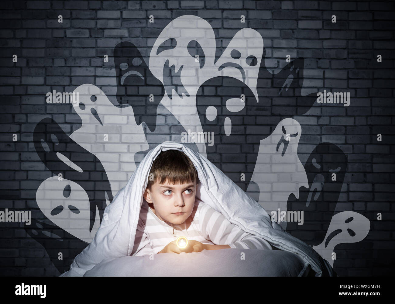 Frightened child with flashlight hiding under blanket. Halloween scary ghostly monsters on wall. Scared kid in pajamas lying in his bed at home. Fear Stock Photo